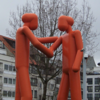 Image shows giant plastic sculpture of two abstract humans shaking hands.