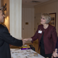 Images shows folks at a networking event shaking hands.